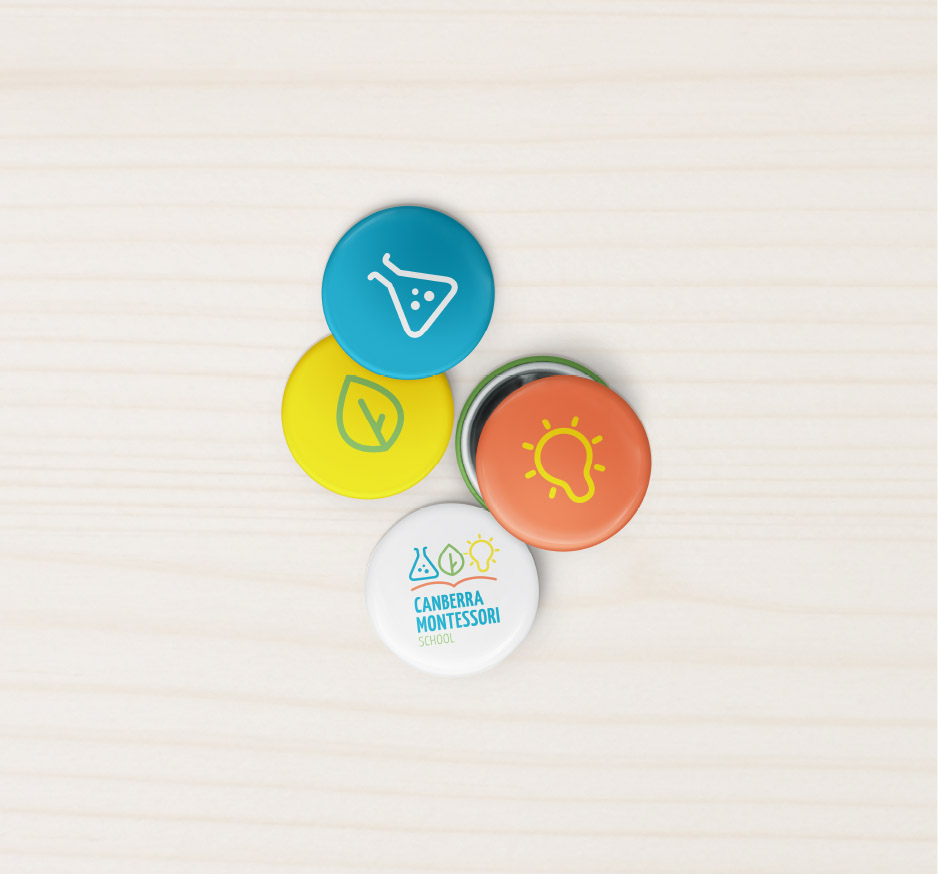 Canberra Montessori School pin buttons with logo and icons on a wooden background