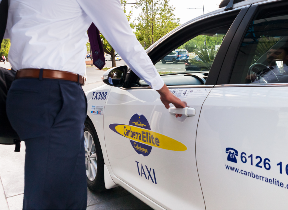 Image of a business man opening a Canberra Elite taxi door with logo